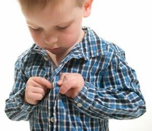 foto de niño abrochando botones para desarrollar la psicomotricidad fina